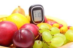 Frische Früchte und Glukosemeter auf hölzerner Platte Stockfotografie