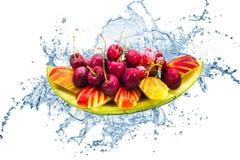 Frische Frucht auf kreativem Spritzenwasser in lokalisiertem Hintergrund Lizenzfreies Stockfoto