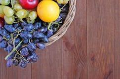 Frische Frucht im Korb auf dem Holztisch Stockbild