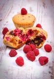 Frische gebackene Muffins mit Schokolade und Himbeeren auf hölzernem Hintergrund, köstlicher Nachtisch Stockfoto