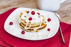 Frische gebackene Muffins zum Frühstück in der weißen Platte, verziert mit Sauerrahm- und lingonbeeren, Stockbilder