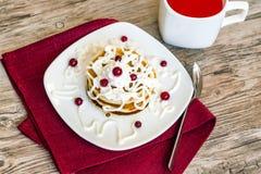 Frische gebackene Muffins zum Frühstück in der weißen Platte, verziert mit Sauerrahm- und lingonbeeren, Lizenzfreies Stockbild