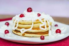 Frische gebackene Muffins zum Frühstück in der weißen Platte, verziert mit Sauerrahm- und lingonbeeren, Stockfotos