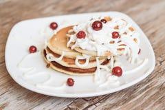 Frische gebackene Muffins zum Frühstück in der weißen Platte, verziert mit Sauerrahm- und lingonbeeren, Stockfoto