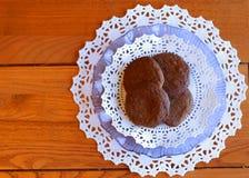 Frische gebackene Plätzchen auf Lavendelplatte mit weißen Doilies auf einer hölzernen Tabelle Stockfotografie