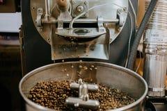 Frische gebratene nat?rliche Kaffeebohnen, welche aus industriellem Kaffee Bean Roaster Machine Inside heraus die Kaffeestube kas lizenzfreie stockbilder