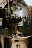 Frische gebratene nat?rliche Kaffeebohnen, welche aus industriellem Kaffee Bean Roaster Machine Inside heraus die Kaffeestube kas lizenzfreie stockfotografie