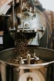 Frische gebratene nat?rliche Kaffeebohnen, welche aus industriellem Kaffee Bean Roaster Machine Inside heraus die Kaffeestube kas lizenzfreies stockfoto