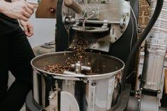 Frische gebratene nat?rliche Kaffeebohnen, welche aus industriellem Kaffee Bean Roaster Machine Inside heraus die Kaffeestube kas lizenzfreie stockfotos