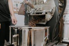 Frische gebratene nat?rliche Kaffeebohnen, welche aus industriellem Kaffee Bean Roaster Machine Inside heraus die Kaffeestube kas stockbilder