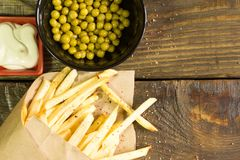 Frische gebratene Pommes-Frites mit Majonäse und Erbsen auf hölzernem Hintergrund Ein strukturierter Hintergrund Kopieren Sie Pas Stockbilder