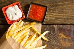 Frische gebratene Pommes-Frites mit Salsa und Majonäse auf hölzernem Hintergrund Ein strukturierter Hintergrund Kopieren Sie Past stockfotos