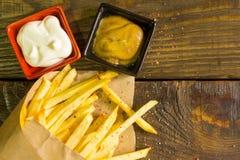 Frische gebratene Pommes-Frites mit Senf und Majonäse auf hölzernem Hintergrund Ein strukturierter Hintergrund Kopieren Sie Paste Lizenzfreies Stockfoto