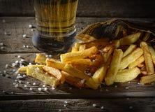 Frische gebratene Pommes-Frites und Bier auf einem hölzernen Hintergrund Lizenzfreie Stockfotografie