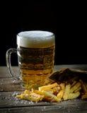 Frische gebratene Pommes-Frites und Bier auf einem hölzernen Hintergrund Stockbild