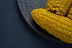 Frische gekochte gelbe Maiskolben liegen auf einem grauen Teller stockbilder