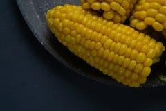 Frische gekochte gelbe Maiskolben liegen auf einem grauen Teller lizenzfreie stockbilder