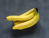 Frische gelbe Bananen auf der dunklen Tabelle Stockfotos