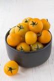 Frische gelbe Tomaten auf weißem Holztisch Lizenzfreie Stockbilder