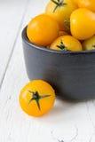 Frische gelbe Tomaten auf weißem Holztisch Stockbild