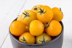 Frische gelbe Tomaten auf weißem Holztisch Stockfotografie