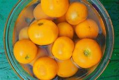 Frische gelbe Tomaten in einer Schüssel Wasser Stockfotografie