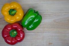 Frische Gemüsepaprikas auf hölzernem Hintergrund stockfoto