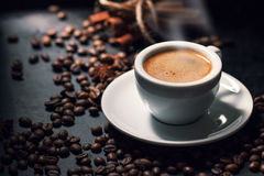 Frische geschmackvolle Espressoschale heißer Kaffee mit Kaffeebohnen auf Dunkelheit Stockfoto