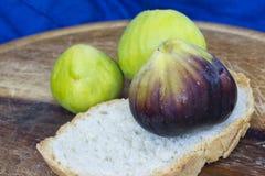 Frische geschmackvolle Feigen trägt auf einer hölzernen Platte mit einem blauen Hintergrund Früchte Stockbild