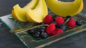 Frische gesunde Frucht auf einem Glasnachtischteller auf schwarzem Hintergrund Gesundes Essenkonzept Lizenzfreie Stockfotos