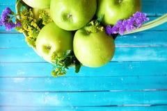 Frische grüne Äpfel mit Blumen im Korb Lizenzfreie Stockbilder
