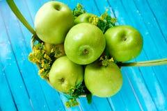 Frische grüne Äpfel mit Blumen im Korb Stockfotos