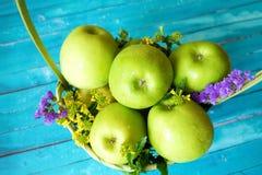 Frische grüne Äpfel mit Blumen im Korb Lizenzfreie Stockfotografie