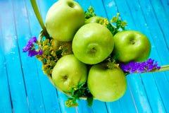 Frische grüne Äpfel mit Blumen im Korb Stockfotografie