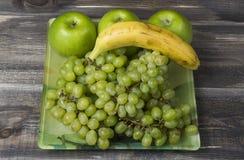 Frische grüne Äpfel, Traube und Banane auf Holz Lizenzfreies Stockbild