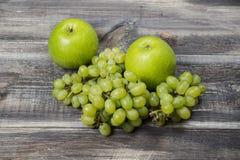Frische grüne Äpfel und Traube auf Holz Lizenzfreie Stockfotos