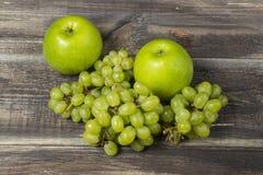 Frische grüne Äpfel und Traube auf Holz Lizenzfreies Stockfoto