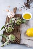 Frische grüne Artischocken auf dem Schneidebrett kochfertig und den Bestandteilen Knoblauch, Zitrone und Olivenöl Stockfoto