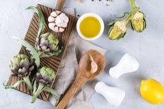 Frische grüne Artischocken auf dem Schneidebrett kochfertig und den Bestandteilen Knoblauch, Zitrone und Olivenöl Stockbild