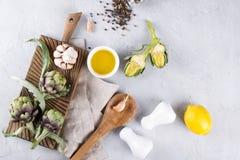 Frische grüne Artischocken auf dem Schneidebrett kochfertig und den Bestandteilen Knoblauch, Zitrone und Olivenöl Stockbilder
