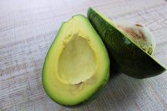 Frische grüne Avocado schnitt zur Hälfte mit dem Chefmesser auf einem weißen Holztisch als Hintergrund in der Küche stock abbildung
