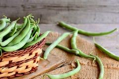 Frische grüne Bohnen in einem braunen Weidenkorb auf einem hölzernen Brett und einem Leinwandgewebe Rustikaler hölzerner Hintergr Lizenzfreie Stockfotos