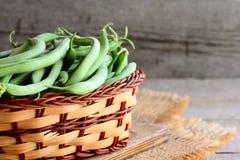 Frische grüne Bohnen in einem Weidenkorb und auf einem hölzernen Brett Unausgereifte grüne Bohnen, organische Quelle von Ballasts Stockbilder