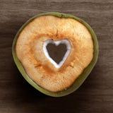 Frische grüne junge Kokosnuss mit herausgeschnittener Herzform lokalisiert auf weißem Hintergrund Stockbild