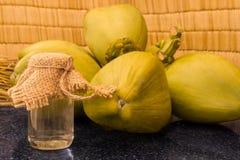 Frische grüne Kokosnüsse verzweigen sich und Kokosnussöl in einem Glas auf schwarzem Granit Stockfoto