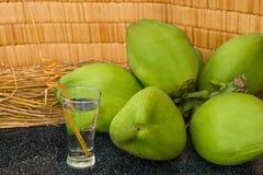 Frische grüne Kokosnüsse verzweigen sich und Kokosnusssaft in einem Glas auf schwarzem Granit Stockbild