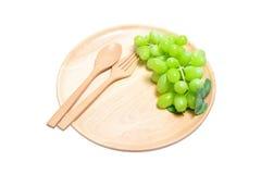 Frische grüne Trauben der hölzerne Teller der Umhüllung, Zusammensetzung lokalisiert über dem weißen Hintergrund Lizenzfreies Stockfoto