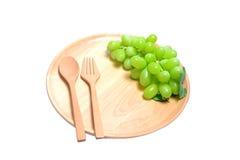 Frische grüne Trauben der hölzerne Teller der Umhüllung, Zusammensetzung lokalisiert über dem weißen Hintergrund Lizenzfreie Stockfotografie