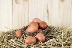 Frische Hühnereien im Stroh nisten auf hölzernem Weinlese backgroun Stockbild