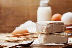 Frische Hefe und Bestandteile für Ostern-Backen auf rustikalem Küchentisch stockfotografie